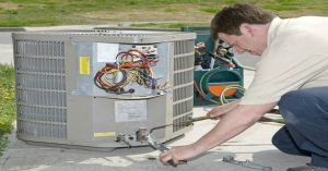 HVAC repairman working on an exterior air conditioning unit