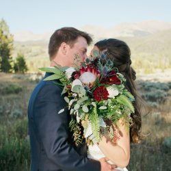 Kissing with a wedding bouquet.