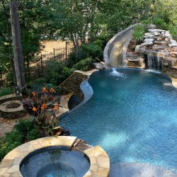 Pool with waterfall, slide, and hot tub.