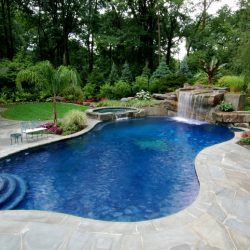 Pool with waterfall, steps, and lush landscaping.