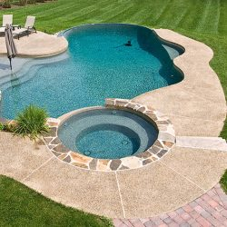 Curvy swimming pool with hot tub.