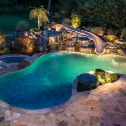 Luxury pool at night with slide.