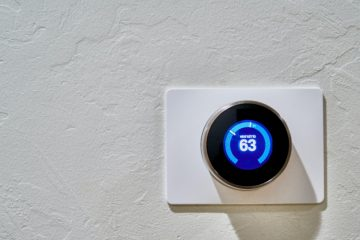 A thermostat on a white wall for an air conditioning system