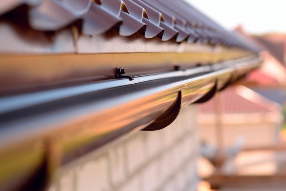 close image of clean gutter on brick house with metal shingles