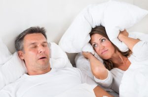 Man snoring, woman covering ears