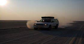 Truck driving on dusty road in the desert