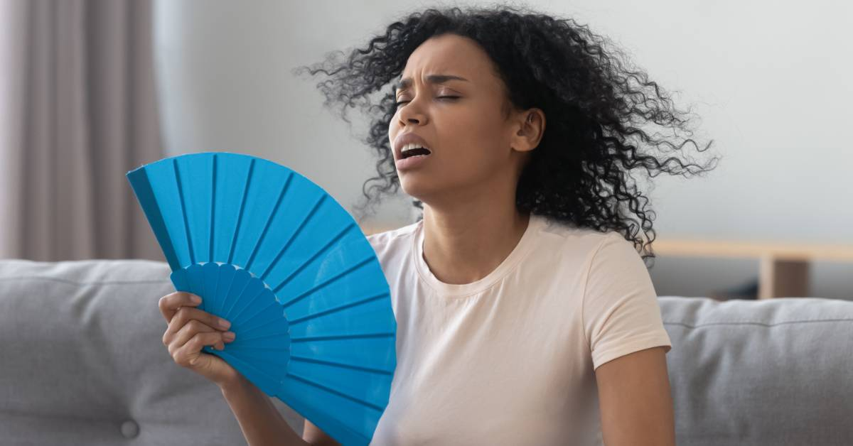 An image of a woman fanning herself.