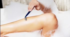 Image of a woman in bathtub shaving leg.