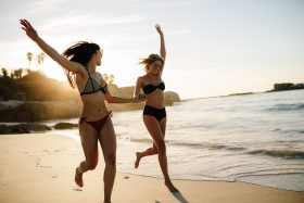 Two women holding hands and skipping on a beach