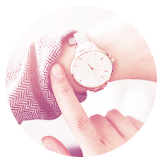 Woman looking at white and silver watch.