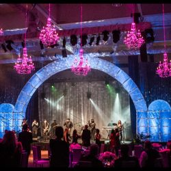 Blue stage lighting and pink chandeliers with custom event lighting