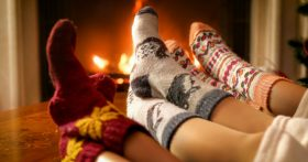 An image of kids in socks warming their feet by a propane fireplace