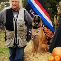 A German Shepherd winning an award with its owner - Canine Oasis
