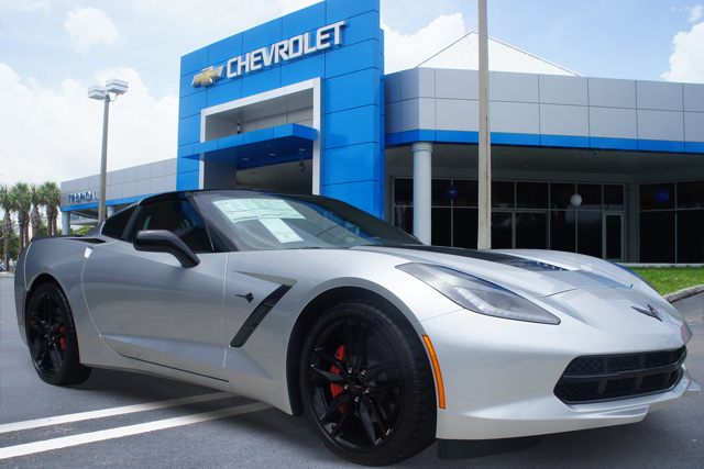 Black and Silver Chevy Corvette in front of a Chevy Dealer by CarData