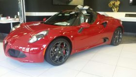 Red Alfa Romeo Spider in a showroom by CarData