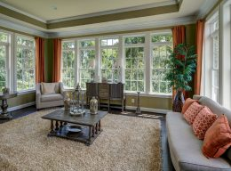 The interior home design of a room built by CarrHomes in Hamilton with three walls of windows.