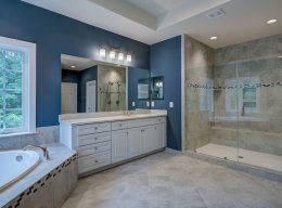 The interior of a CarrHomes luxury home bathroom with a tiled shower, bathtub, and sink.