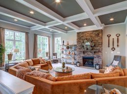 A family room with an orange couch and large windows, designed by CarrHomes home builders in Hamilton.