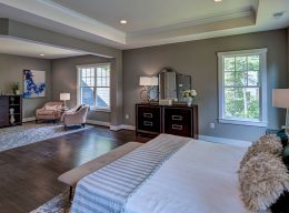 A large bedroom with seating area staged from the interior home design from CarrHomes in Hamilton.