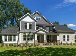 The exterior of a white, grey, and tan house from CarrHomes home builders in Hamilton.