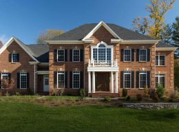 The outside of a CarrHomes designer home made with red brick and a second story balcony.