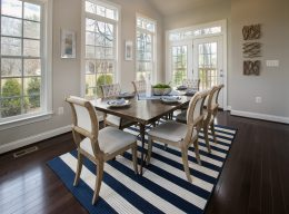 The interior house design of a dining room with chairs, a table, and a rug from CarrHomes in Hamilton.