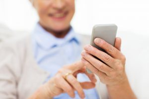 technology, communication age and people concept - close up of happy senior woman with smartphone texting message at home