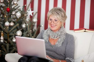 Attractive glamorous senior woman sitting in her living room in front of a decorated Christmas tree using a laptop, red and white themed