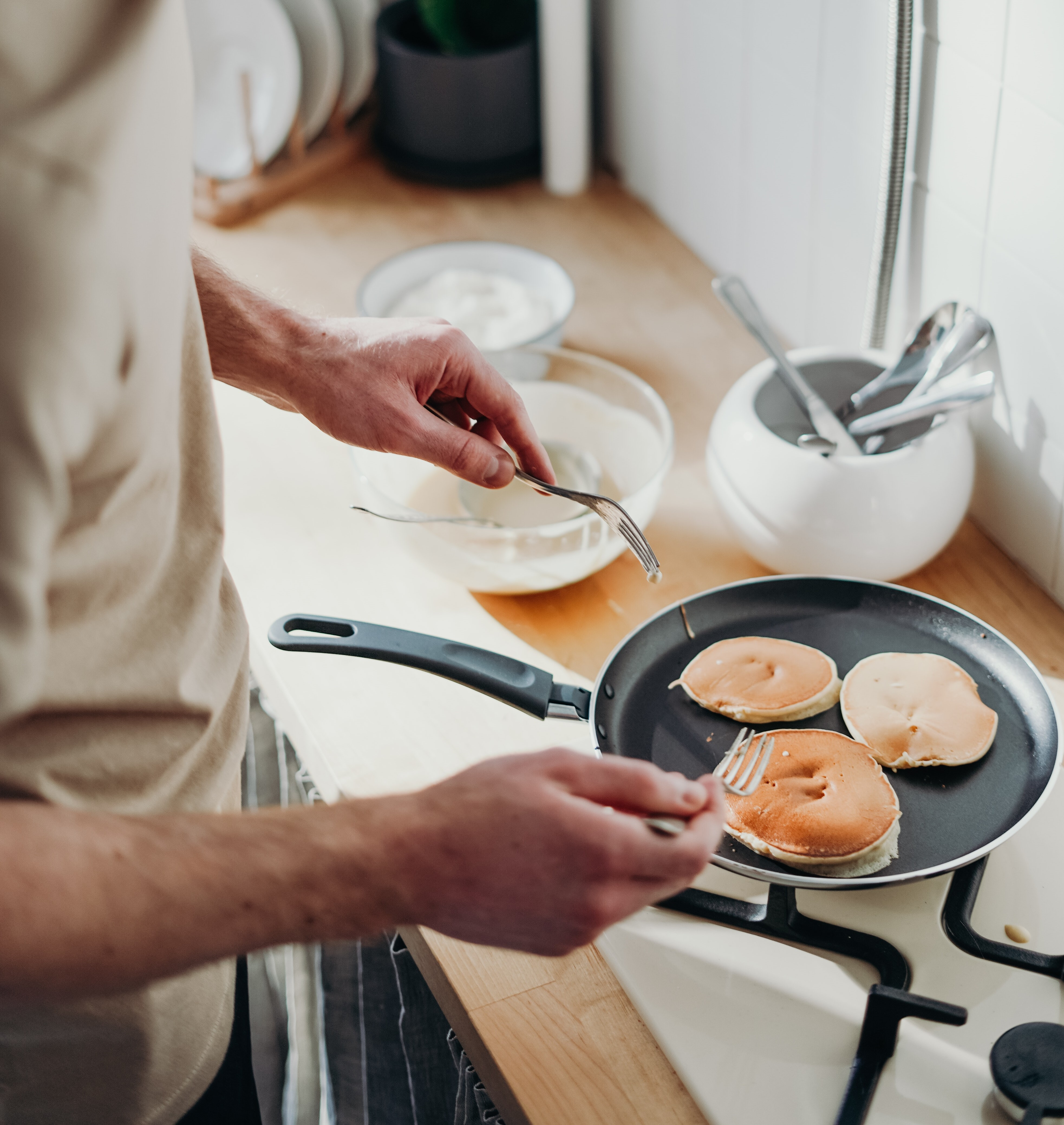 man making pancakes on the stove