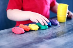 Closeup of young child in a red shirt playing with rainbow Playdoh