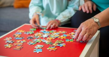 Close up shot of child and adult hands working on a puzzle