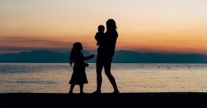 Silhouette of a family by the water right after sunset.