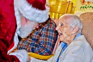 A resident is thrilled to see Santa at the Holiday Open House
