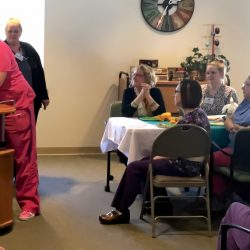 Happy staff embrace at awards event at memory care facility in Vermont