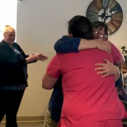 Employees hug one another at an assisted living center in Windsor