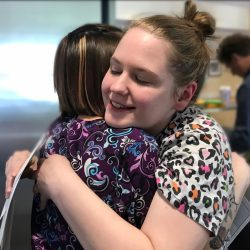 Happy staff members embrace at independent living community in Windsor