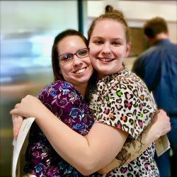 Two staff members hug at assisting living home in Windsor