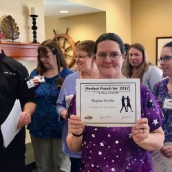 Proud staff member holds up award at senior living community in Windsor