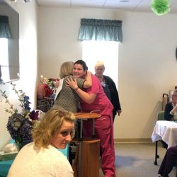 Hugs between staff at assisted living center in Windsor