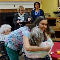 Staff hugs resident at award ceremony at retirement community in Windsor