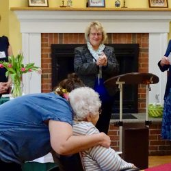 Staff gives out hugs during celebration at retirement community in Windsor