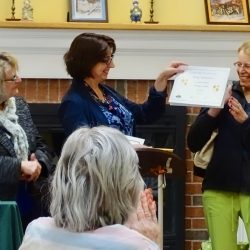 Staff member smiles as she receives award from retirement home in Windsor
