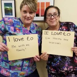staff of senior living community in Windsor pose with posters