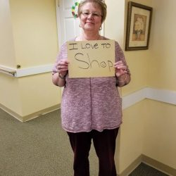 Leader at assisted living care center in Windsor holds up sign