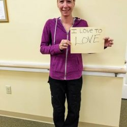 Staff member at Vermont memory care center poses with poster