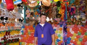 Image of Carnival Games Manager In Front Of Prizes