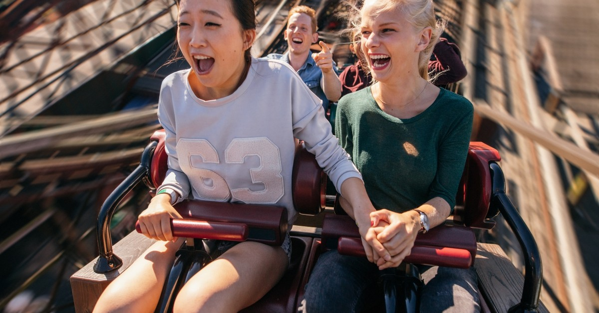 Image of two friends holding hands on a wooden roller coaster
