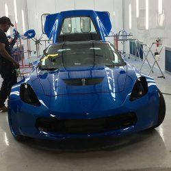 Blue skeleton of sports car inside spray booth
