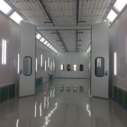 Elongated interior of glossy white spray booth