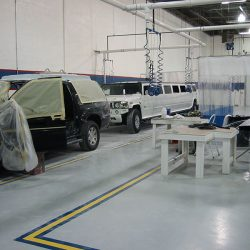 Whie limo and black SUV preparing for paint job